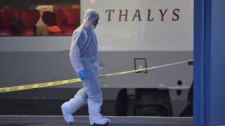A man in a forensic suit walks near the crime scene in front of a Thalys train in August 2015