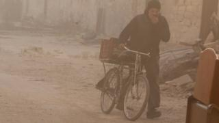 A man covers his face from dust as he walks with a bicycle after a strike on the rebel held besieged al-Shaar neighbourhood of Aleppo, 26 November.