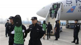 In this photo released by Xinhua News Agency, Chinese suspects involved in wire fraud are escorted off a plane upon arriving at the Beijing Capital International Airport in Beijing on Wednesday, April 13, 2016.