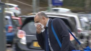 Rajesh Lama arriving at Newport Crown Court - he is trying to hide his face with a tissue. He is wearing a suit and had a blue holdall bag over his shoulder