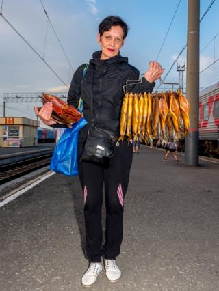 A woman sells smoked fish on the platform at Barabinsk in Russia