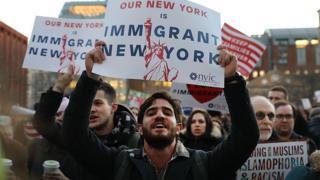 Manifestantes exibem cartazes pro-imigrantes em Nova York