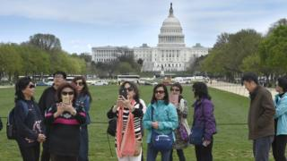 A group of Chinese tourists take photographs on the National Mall with the U.S. Capitol in the background