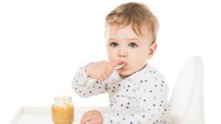 Toddler eating a jar of baby food