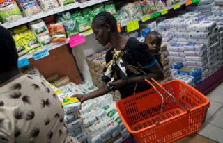 A woman buys a packet of maize flour subsidised by government at a supermarket in Nairobi, Kenya May 24, 2017.