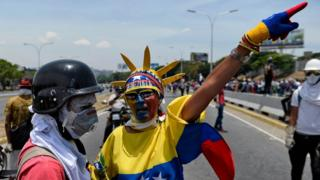 Anti-government protesters take part in a march in Caracas