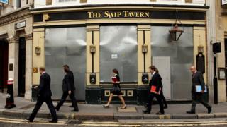 City workers walk past a closed down pub in London's financial district