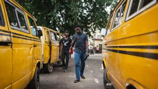 Pokeman Go mania in Nigeria with two young men walking between buses whilst playing the game on their mobile phones