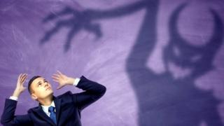 La sombra de un demonio y un hombre vestido de ejecutivo