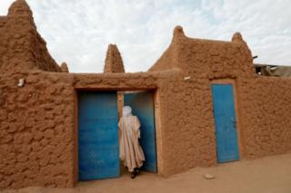 An imam opens a blue door.