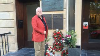 Anthony Kozlowski stands on the steps of the Sikorski Polish club in Glasgow, in front of memorial plaques