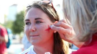 Woman has England flag painted on her cheek