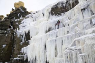 Climber on a frozen over Kinder Downfall