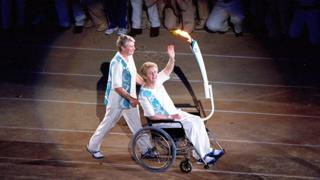Betty Cuthbert is pushed by Raelene Boyle during the Opening ceremony of