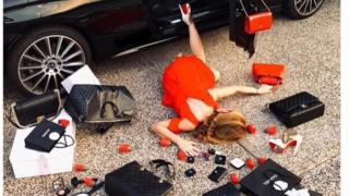 A woman face down having pretended to fall from her car. Luxury items surround her.