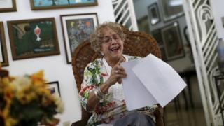 Ileana R. Yarza laughs while holding a print-out of a letter U.S. President Barack Obama is sending her via a flight carrying the first batch of U.S. direct mail to Cuba, after both countries agreed to restore direct postal service after a half-century rupture, at her home in Havana
