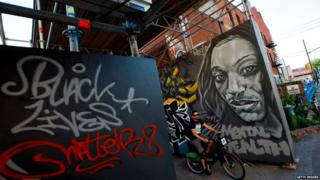 Mural of Regis Korchinski-Paquet along with sign saying Black Lives Matter