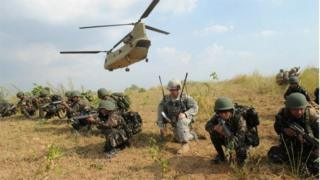 Philippine soldiers and a US Army soldier take their positions after disembarking from a C-47 Chinook helicopter during an exercise at a military training camp in the Philippines (April 2015)