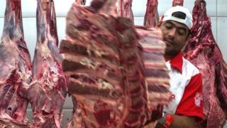 Carne colgando en un frigorífico.