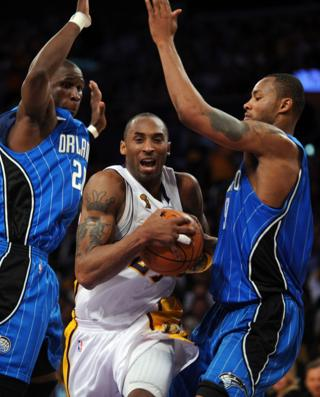 Kobe Bryant outpasses Orlando Magic's Mickael Pietrus and Rashard Lewis during the NBA final between Los Angeles Lakers and Orlando Magic.