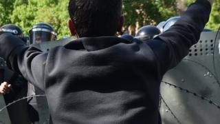A protester holds up his hands in front of a police barricade in the Armenia capital of Yerevan