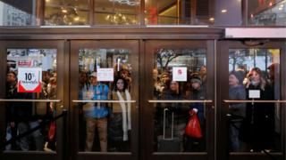 People gather at the Broadway entrance of Macy's Herald Square store ahead of early opening for the Black Friday sales in Manhattan, New York, US