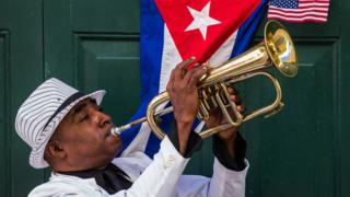 Man playing trumpet in front of Cuban and US flags