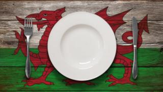 White plate on a table painted with the Welsh flag
