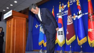 South Korean Defence Minister Jeong Kyeong-doo bows in front of Korean flags at a press conference in June where he offered an apology to citizens over the fishing boat incursion