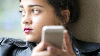 Young girl early teens playing on her phone and texting