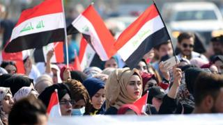 Iraqis wave national flags at a protest in Baghdad on 11 November 2019
