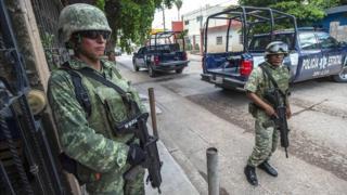 Soldados al lado de vehículos de la policía en México.