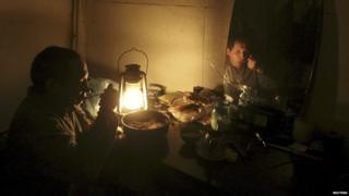Ravshan, a Crimean Tatar, is reflected in a mirror as he eats by the light of a burning oil lamp due to a power cut inside his house in the village of Strogonovka, Simferopol district, Crimea, in this November 26, 2015 file photo