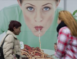 Women walk in front of a commercial featuring a woman eating pasta, outside a restaurant in Berlin