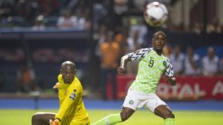 Odion Ighalo wa Nigeria acisha umupira ku munyegoli Jonathan Nahimana w'Intamba mu Rugamba