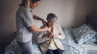 A pensioner being helped to dress