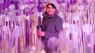 لیوس کیوبک پارک، کنگز کراس میں رامی بیباوی اور کانوا کے تخلیق کردہ فن 'اینٹر لیس رینگز' سے ایک خاتون گزر رہی ہے۔