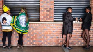Two schoolgirls have a snack as two women wearing African National Congress (ANC) regalia pause at the Orlando stadium in Soweto, Johannesburg, on April 11, 2018.