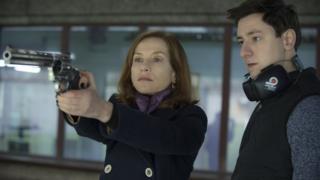 Escena de la película en que la actriz empuña un arma al lado de un instructor.