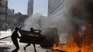 Para pengunjuk rasa memasang penghalang jalan di depan gedung parlemen Rio.