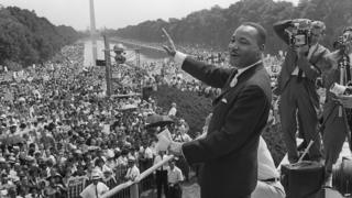 The civil rights leader Martin Luther King (centre) waves to supporters 28 August 1963 on the Mall in Washington DC