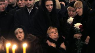 Marina Karlova (seated, R), the widow of killed Russian ambassador to Turkey, Andrei Karlov, and his mother Maria (seated, L) are surrounded by mourners (22 Dec)