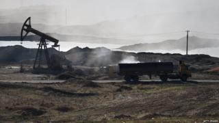 A truck sits near an oil pump in Syria