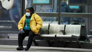 A woman wearing a face mask waits for a tram in Manchester, following the outbreak of the coronavirus disease (COVID-19), Manchester, Britain