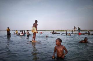 People in Mali bathe in the Niger River before sunset.