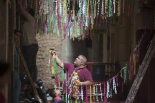 in_pictures Two men hang strings of colourful paper decorations above a narrow street.