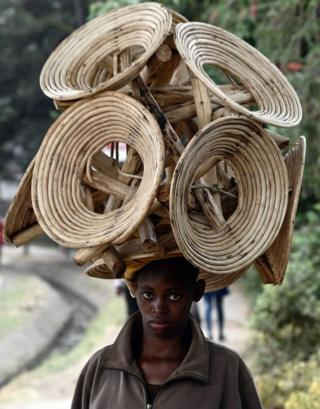 A woman carries several wooden chairs on her head on a street. She is looking directly at the camera.