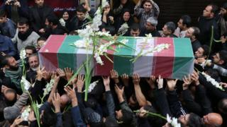 Iranian mourners carry the casket of Revolutionary Guards Corps member Abdollah Bagheri, who was killed fighting in Syria, during his funeral in Tehran