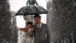 A newly wed couple poses during a photoshoot as snow falls over Paris on 22 January 2019