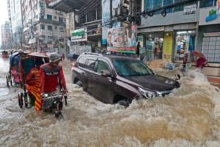 in_pictures Commuters make their way through a water-logged street